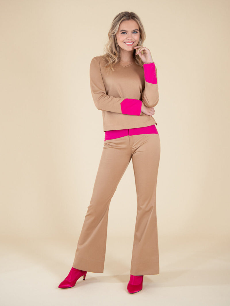 Woman wearing a beige blouse and flared trousers with pink elements