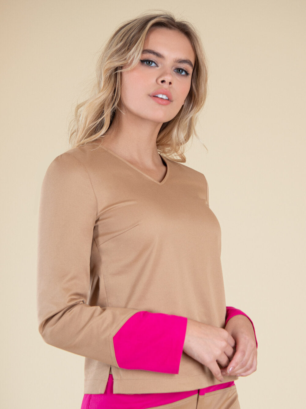 Woman wearing a beige blouse with bright pink elements on the sleeves