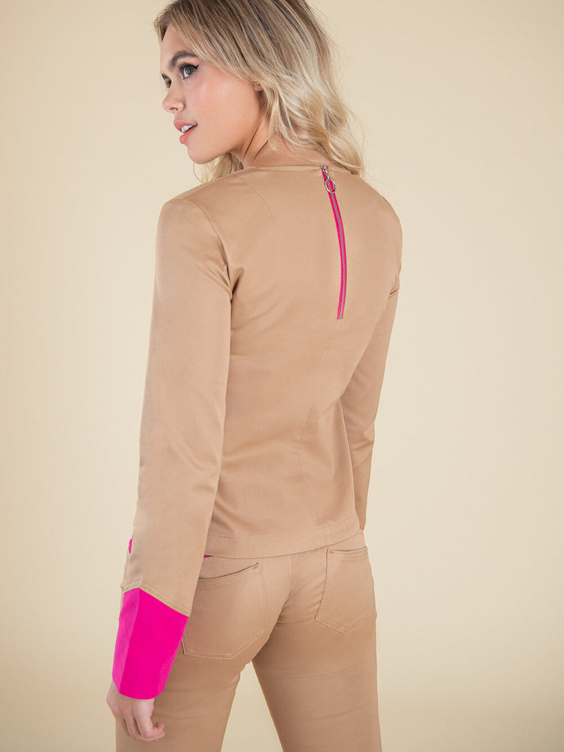 Backshot of a woman wearing a beige blouse with bright pink ciffs and zipper on the back
