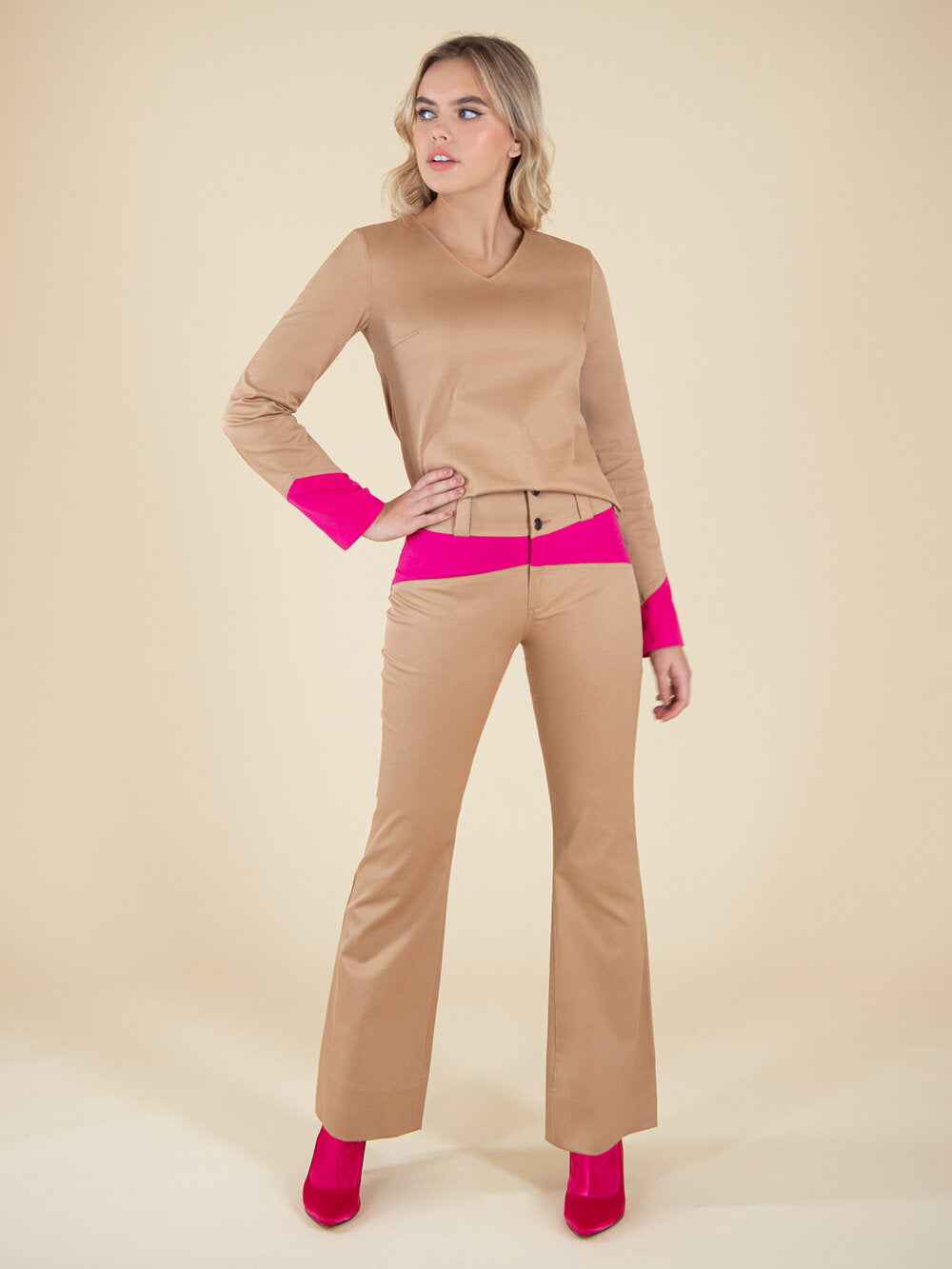 Woman wearing a sustainable beige blouse and flared trousers with neon pink elemenets