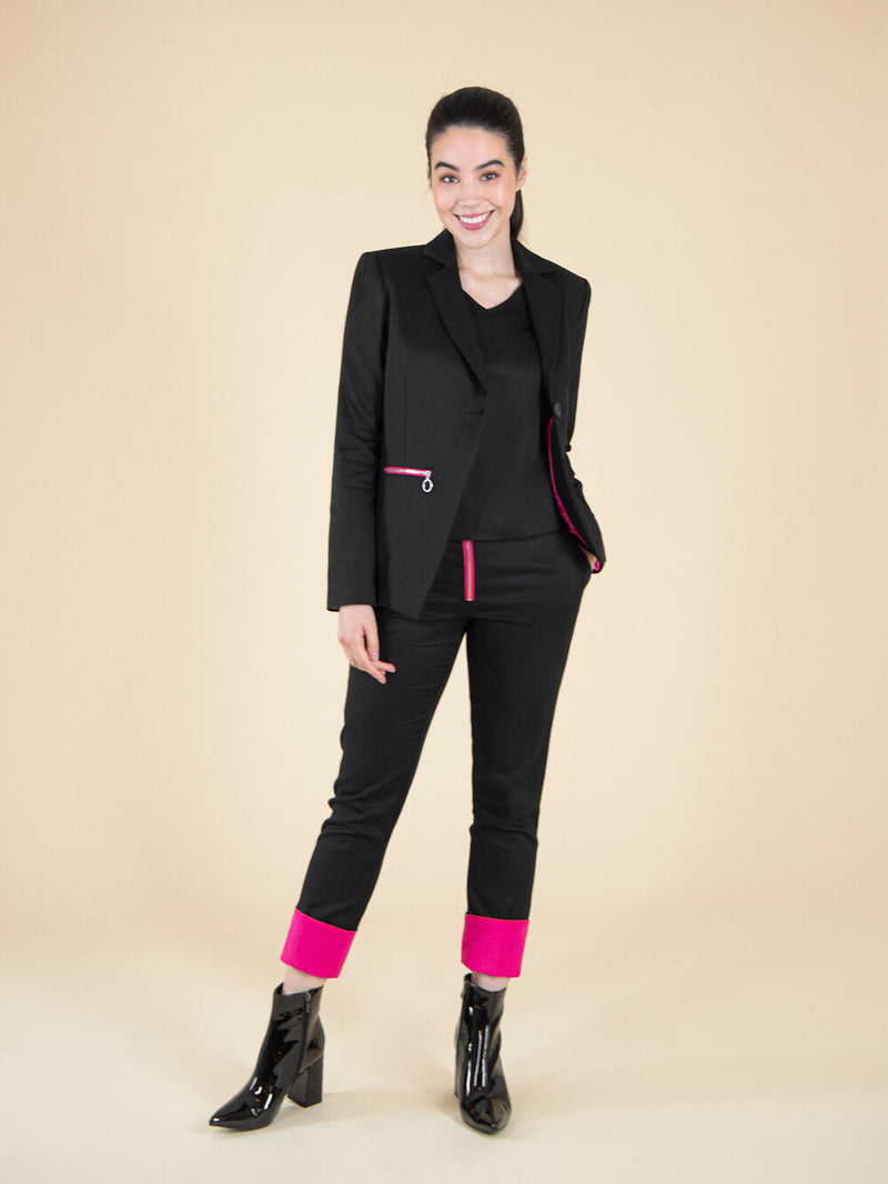 Woman wearing a black sustainable blazer and trousers with bright pink details