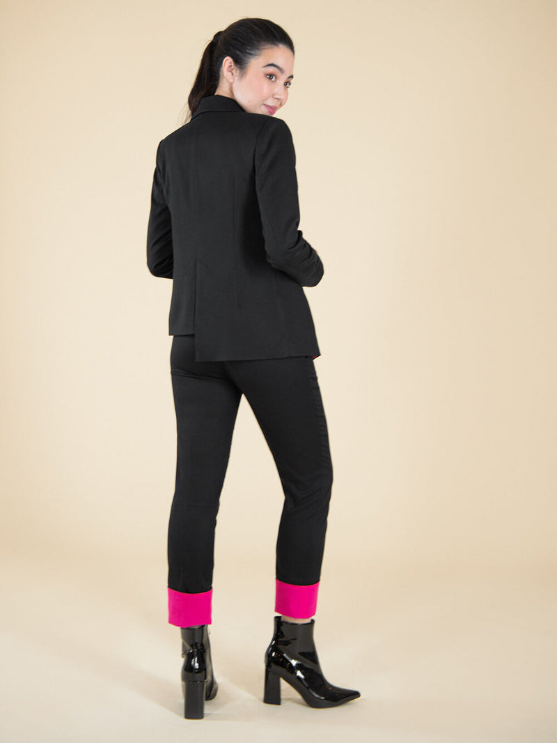 Backshot of a woman wearing a black sustainable upcycled suit with pink details