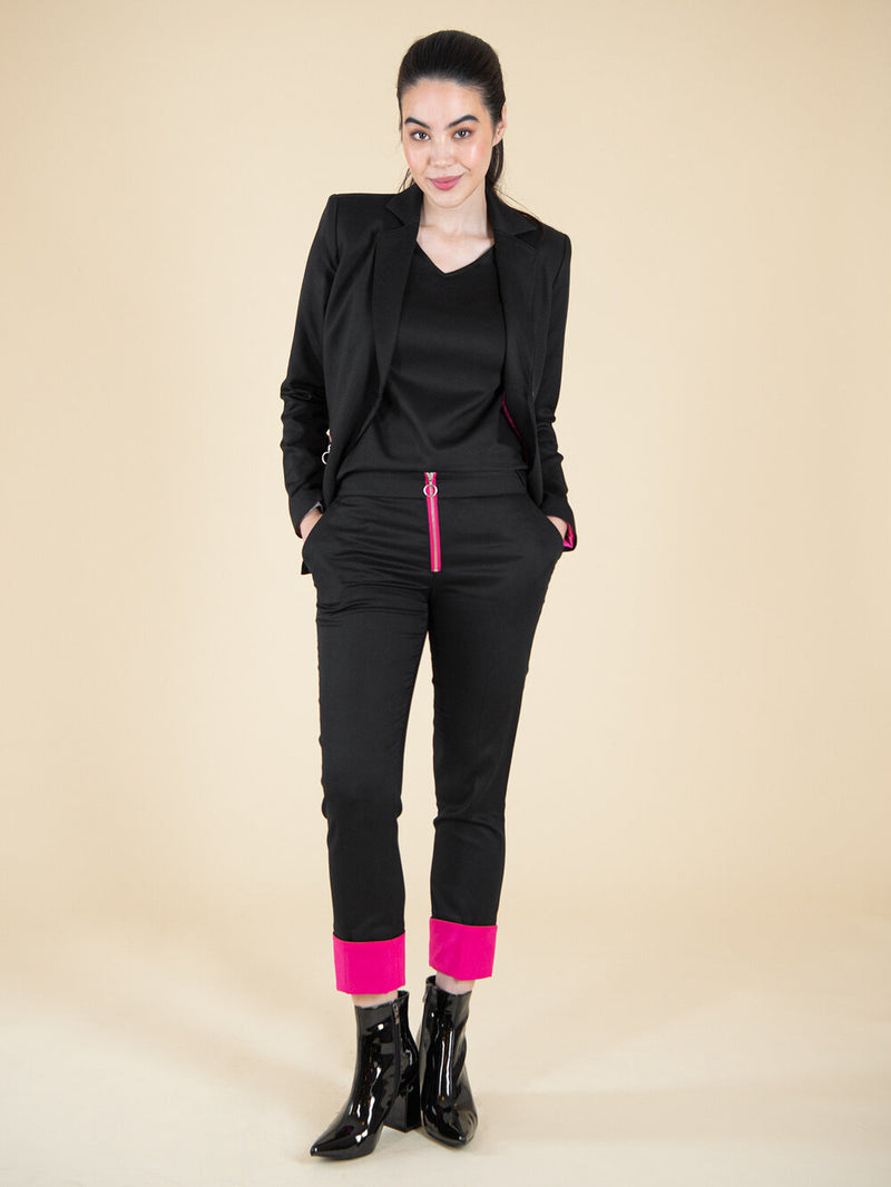 Frontshot of a woman wearing a black upcycled office suit with pink details
