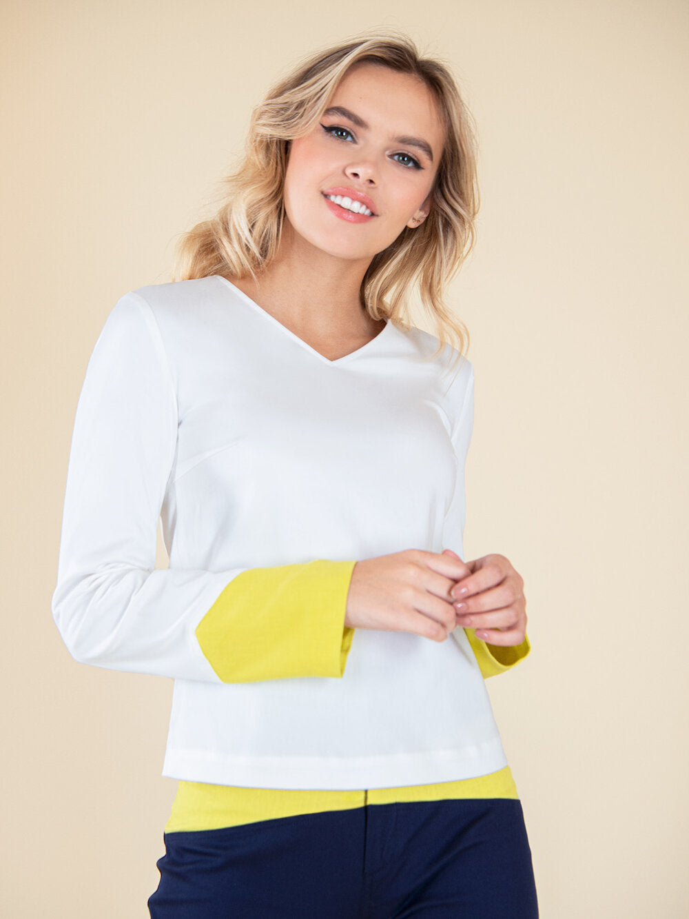 Woman wearing a white blouse with bright yellow elements on the sleeves