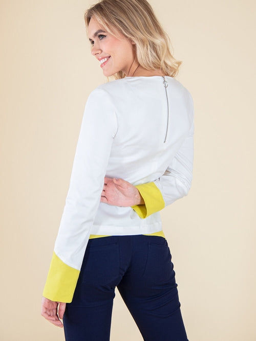 Backshot of a woman wearing a white blouse with electric yellow cuffs