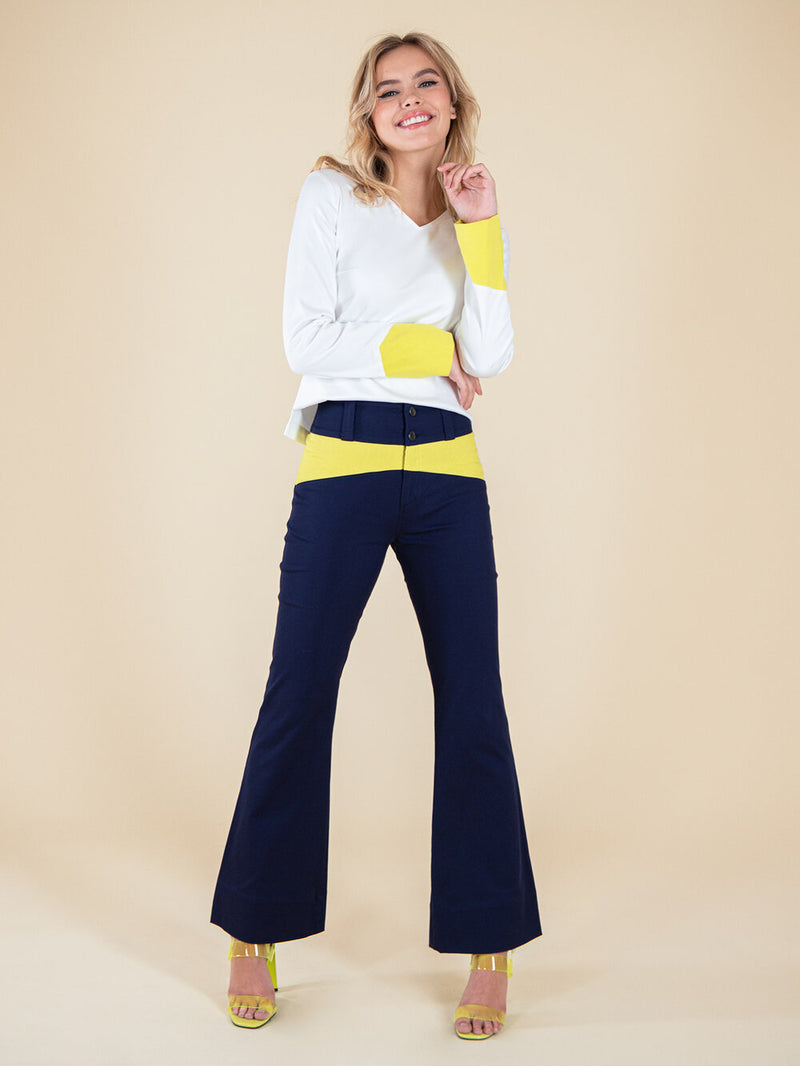 Frontshot of a woman wearing a white blouse and navy blue flared trousers with neon yellow elements