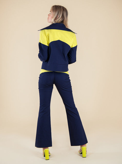 Backshot of a woman wearing upcycled navy blue bomber jacket and flared trousers with yellow elemements