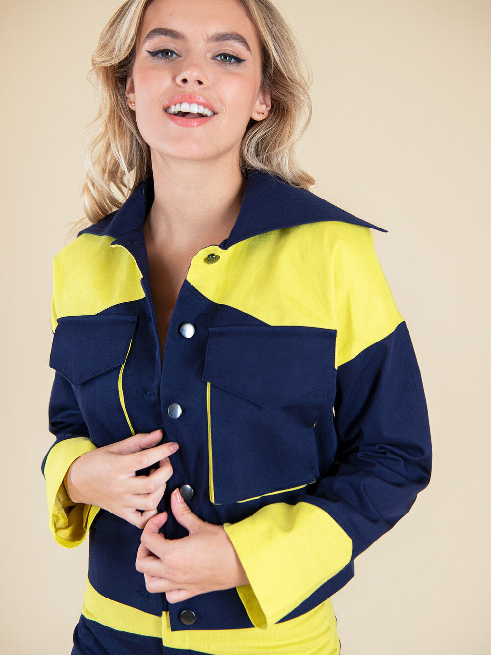 Happy woman wearing a navy blue upcycled bomber jacket with bright yellow details and big front pockets