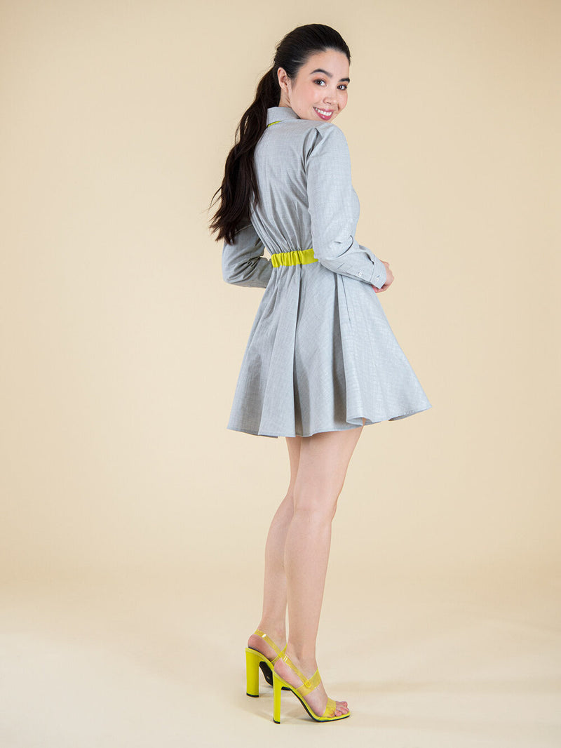 Backshot of a woman wearing a grey dress with yellow belt