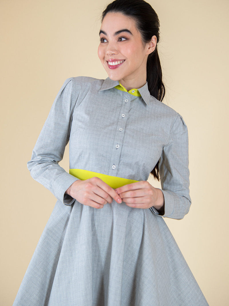 Woman wearing a grey upcycled dress with long sleeves and yellow elements