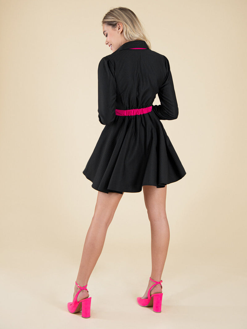 Backshot of a woman wearing a black upcycled dress with bright pink belt