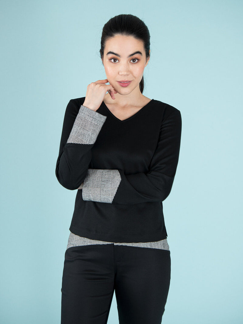 Woman wearing a black office blouse with checker details on the sleeves