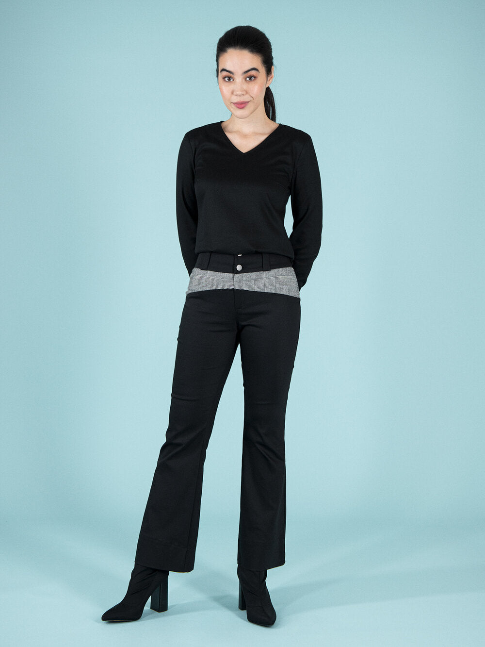 Frontshot of a woman wearing a black sustainable blouse and flared troursers with checker elements