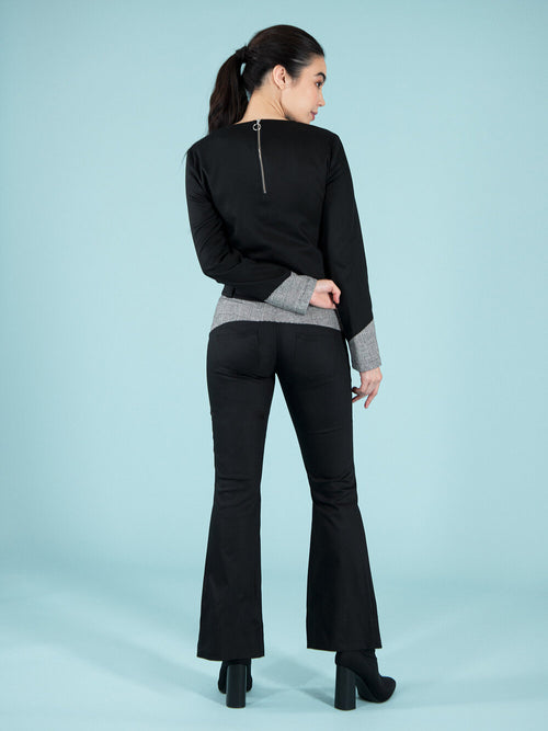 Backshot of a woman wearing a sustainable black blouse and flared trousers with checker details