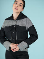 Close shot of a woman wearing a black bomber jacket with checker elements