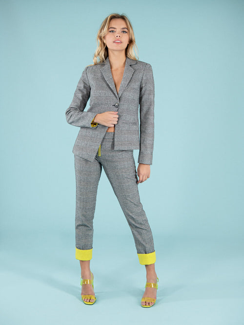 Woman wearing sustainable office blazer and straight trousers with bright yellow details