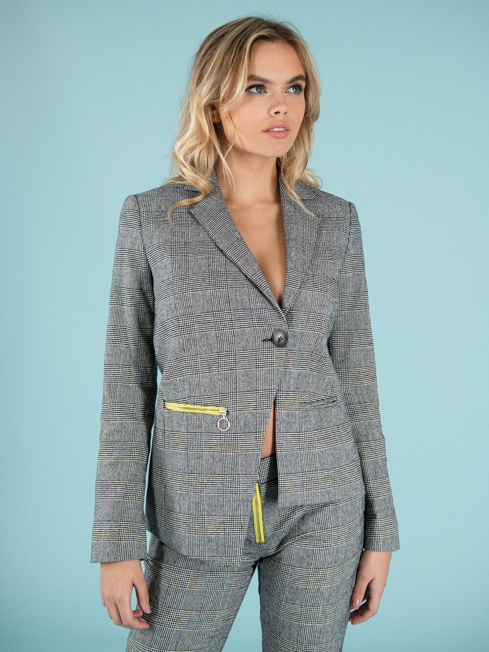 Woman wearing a sustainable blazer with bright yellow zipper