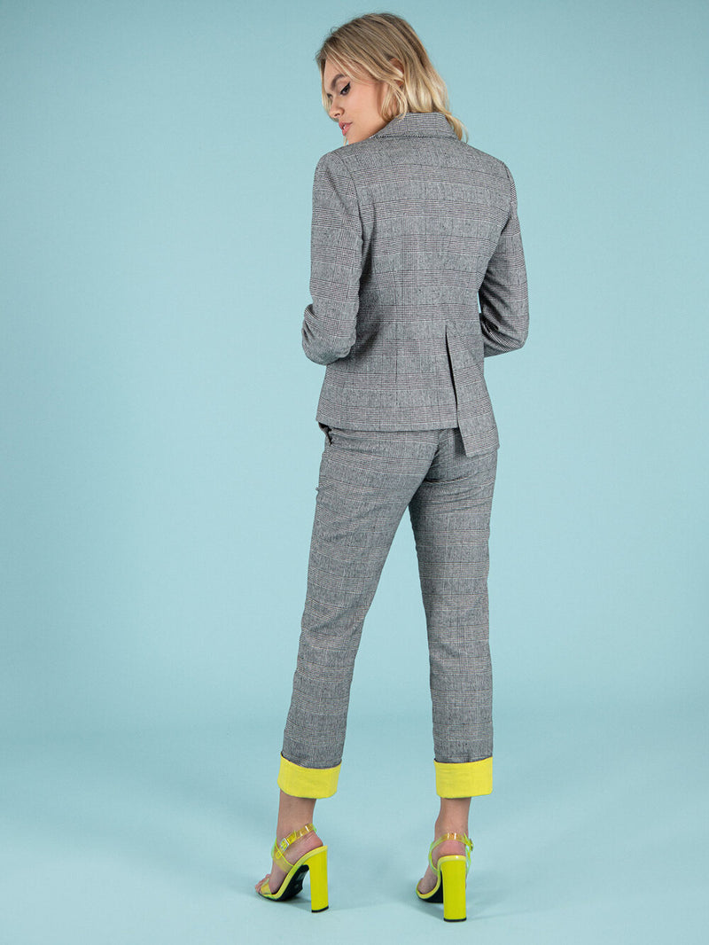 Backshot of a woman wearing a sustainable checker suit with yellow elements