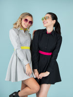 Two women wearing dresses in grey and black with yellow and pink elements