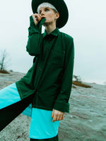 Woman in nature wearing a dark military green oversized shirt with a blue element