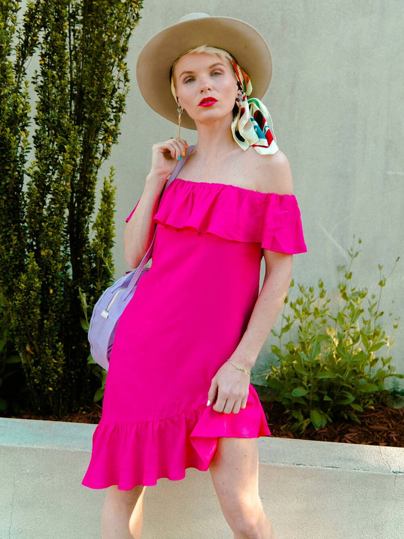 Woman on the street wearing a bright pink summer dress with ruffles