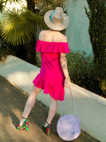 Backshot of a woman wearing a pink summer dress with ruffles
