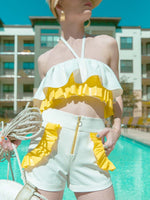 Woman standing in the summer sun wearing a white and yellow ruffled crop top and white shorts with yellow ruffles around the pockets
