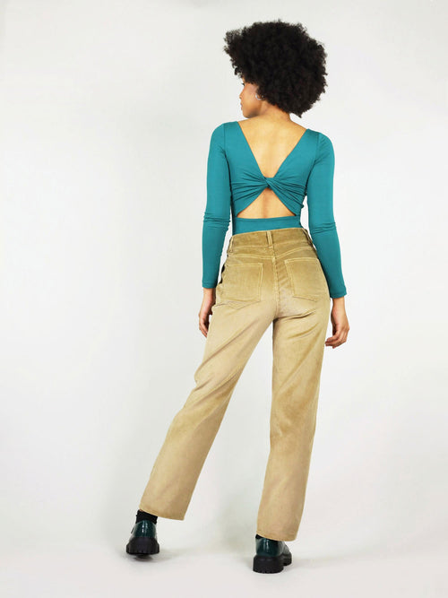 Back shot of the corduroy trousers in colour autumn beige. High waisted trousers with two large pockets on the back and belt loops. Stretchy, comfortable 100% organic cotton.