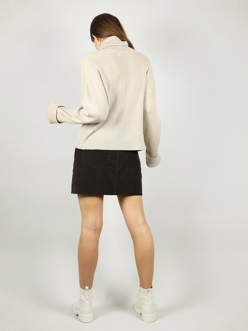 The back view of the turtleneck in beige shows that it has loose fit and extra long sleeves for added comfort. Long roll neck pullover and hips length for extra warmth.