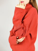 The organic cotton turtleneck has extra long sleeves and comes in bright red. It has comfortable, slightly loose fit.