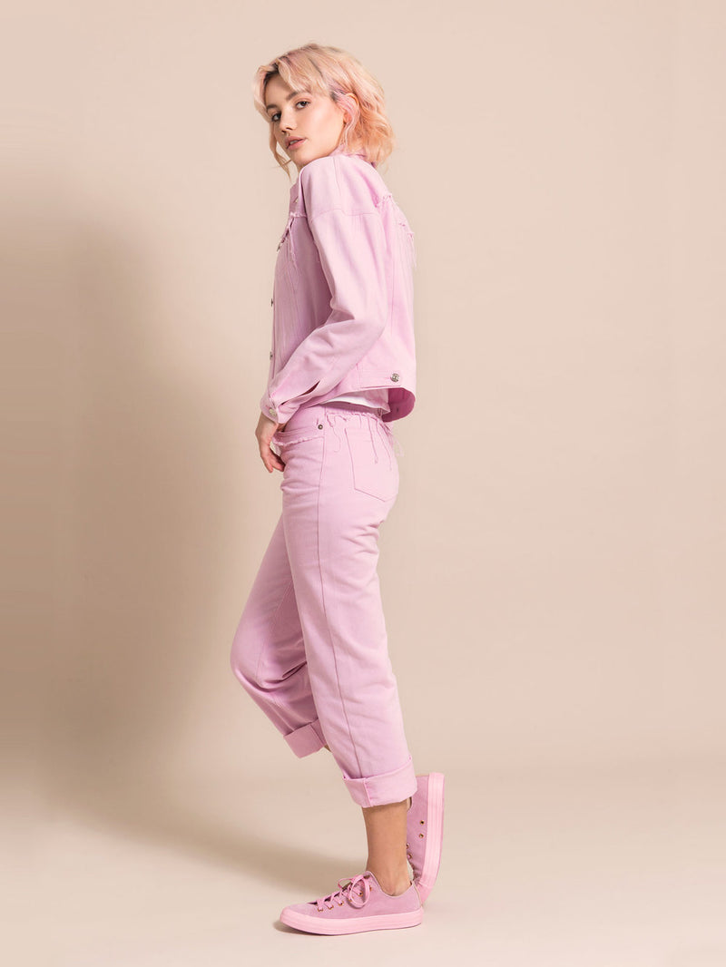 Sideshot of a model wearing a light pink denim set with frayed details