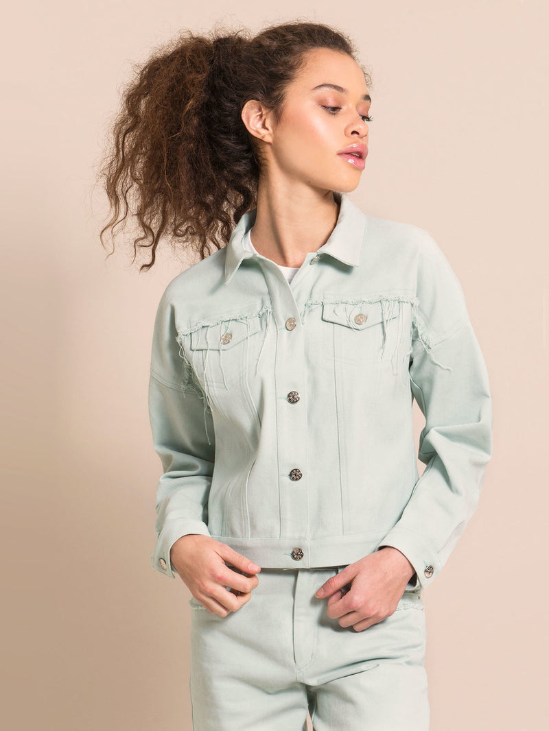 Girl wearing a light blue denim jacket with flared details above the front pockets