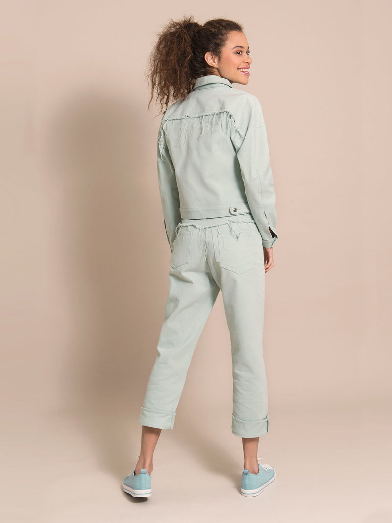 Backshot of a woman wearing a light blue jacket and mom's jeans with frayed details