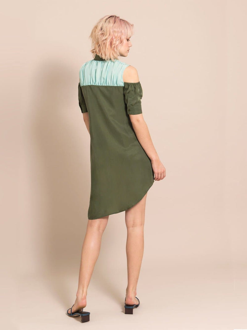 Backshot of a wodel wearing an above-the-knee, assymmetric military green dress made from cupro