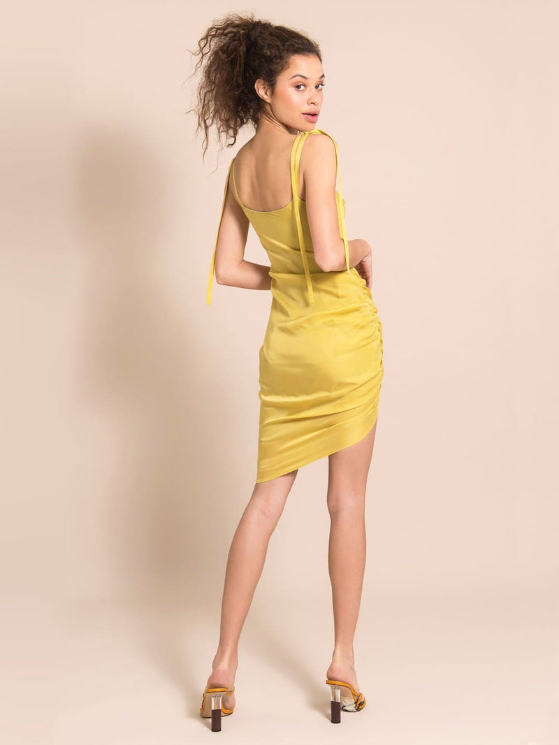 Backshot of a mode wearing a cocktail dress in yellow with adjustable shoulder straps