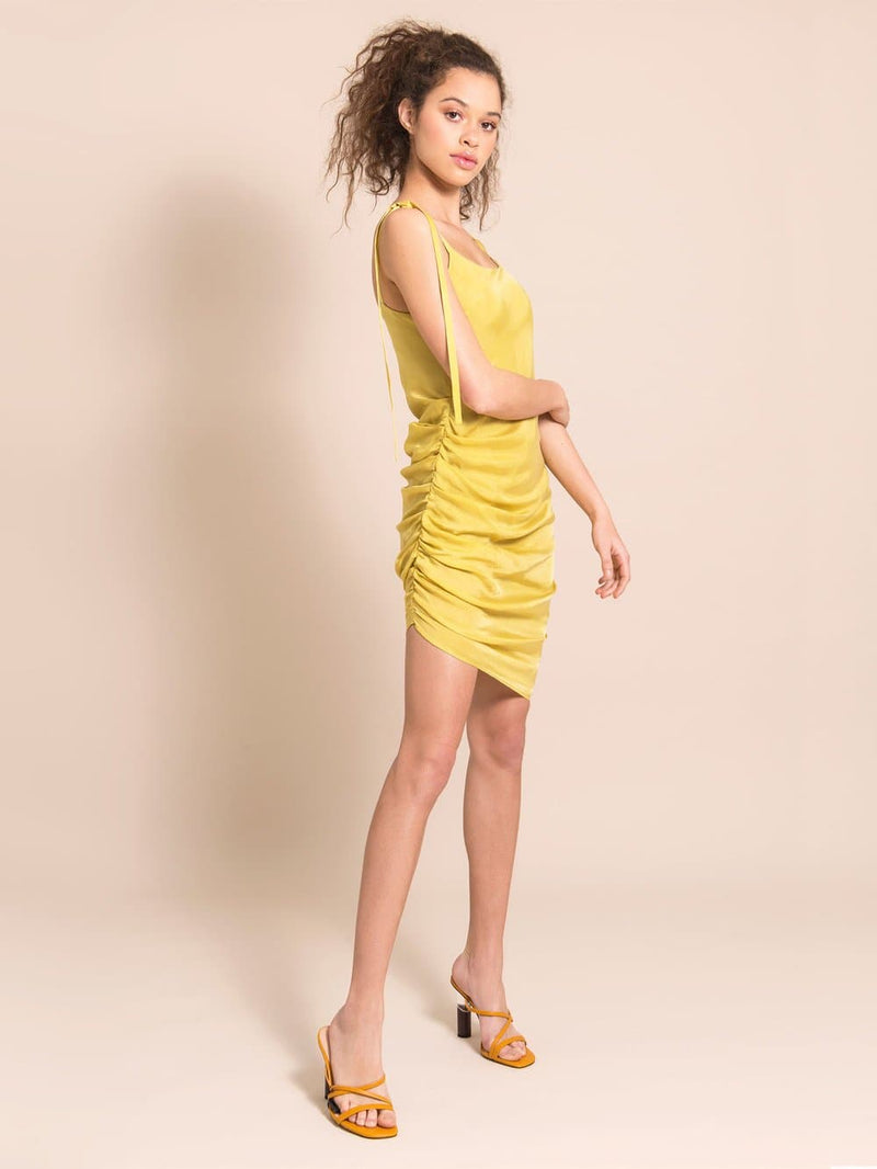 Frontshot of a model wearing a short, cocktail dress in yellow with adjustable shoulder straps. Perfect for wedding, cocktail or party