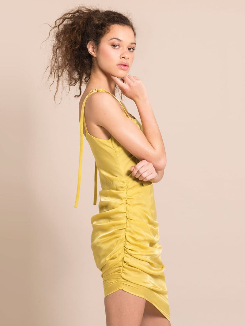 Sideshot of a model wearing a sustainable yellow silky coctail dress with gathers on the side and adjustable shoulder straps