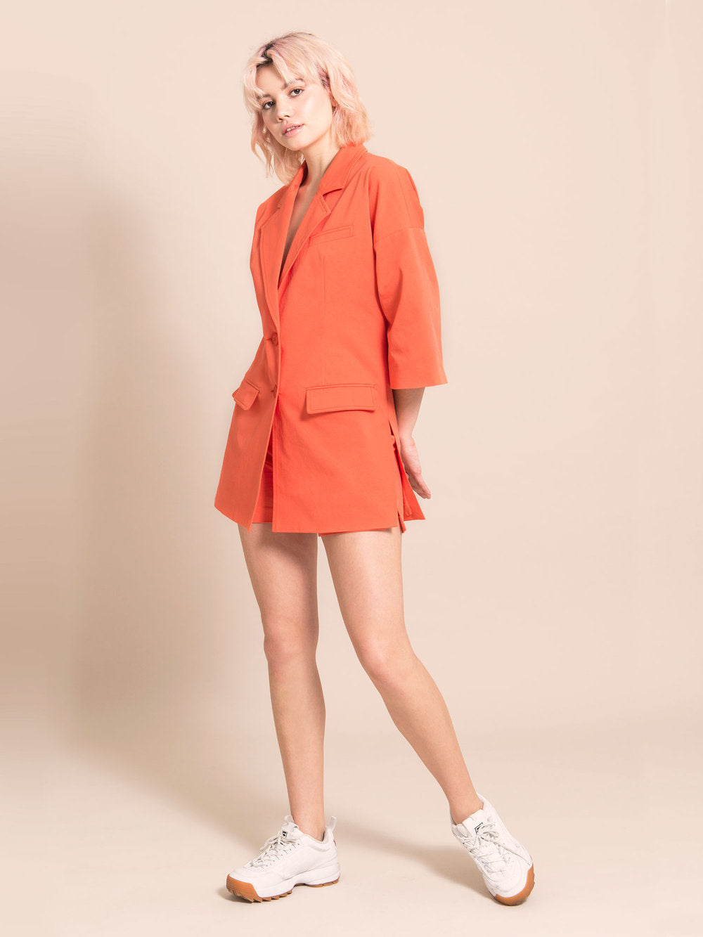 Woman wearing a long orange sustianable blazer