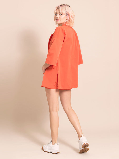 Backshot of a woman wearing a long orange blazer