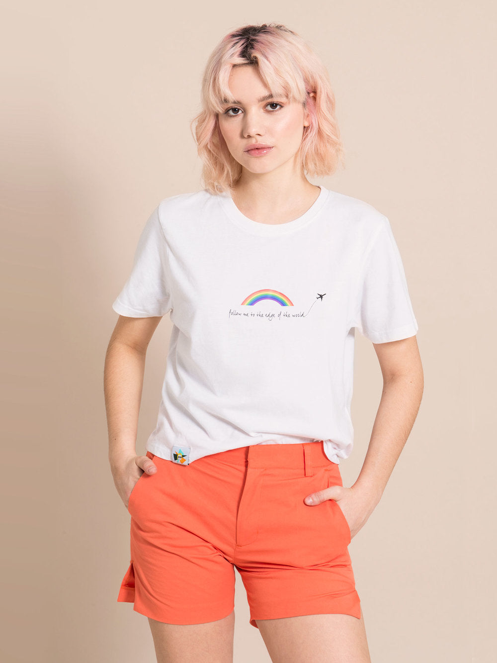 Woman wearing white recycled cotton t-shirt with print and orange shorts with crease