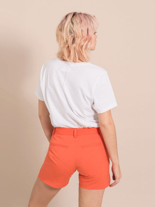Backshot of a woman wearing a white tee and beige shorts