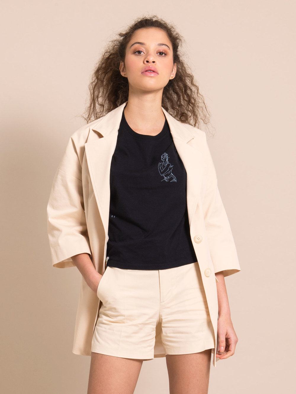 Woman wearing sustainable beige shorts with crease, black tee with print and a long beige blazer with bell sleeves