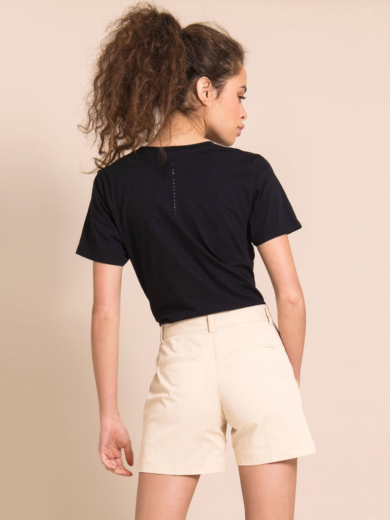 Backshot of a woman wearing a black recycled t-shirt and beige shorts with crease