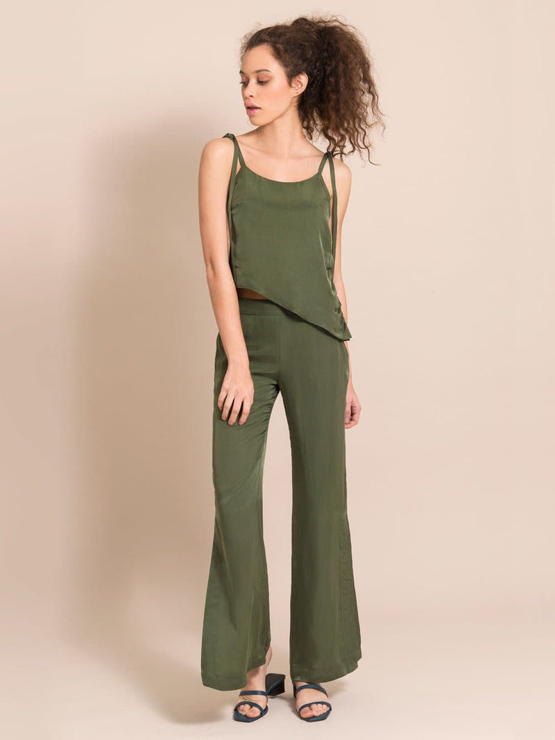 Frontshot of a woman wearing a sustainable military green set - an assymetric top and flared silky trousers