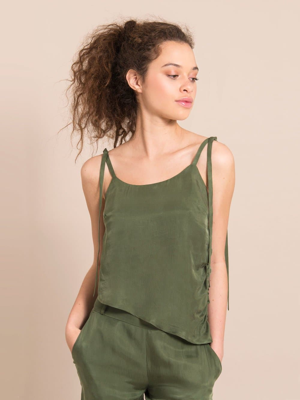 Frontshot of a girl wearing a sustainable  military green assymetric top with adjustable shoulder straps