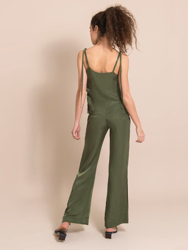 Backshot of a woman wearing a sustainable set in military green - a sleeveless top with adjustable shoulder straps and loose, flared, summer  trousers