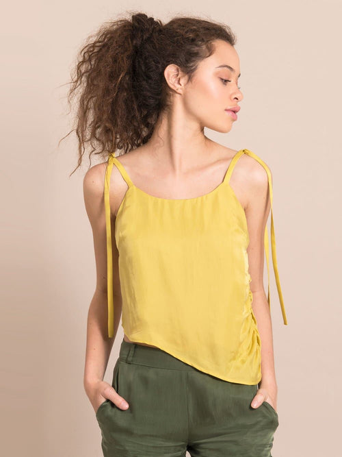 Frontshot of a woman wearing a sustainable  yellow assymetric top with adjustable thin shoulder straps