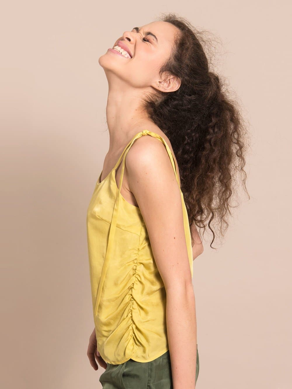 Sideshot of a happy woman wearing a sustainable yellow top with gathers on the side