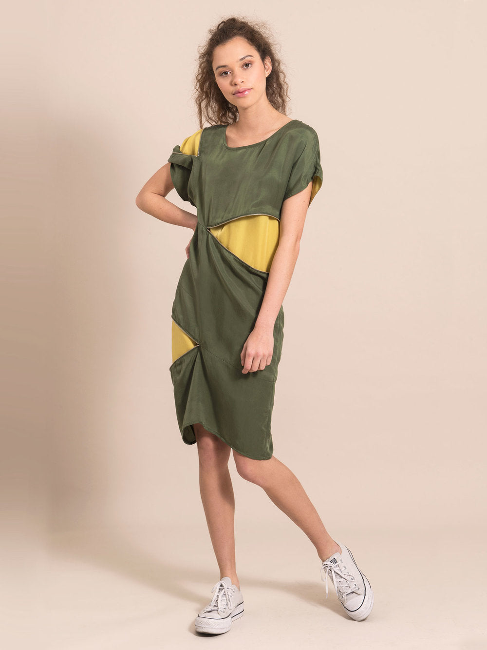 Woman wearing a military green above-the-knee day dress with three zippers that open and expose a bright yellow lining