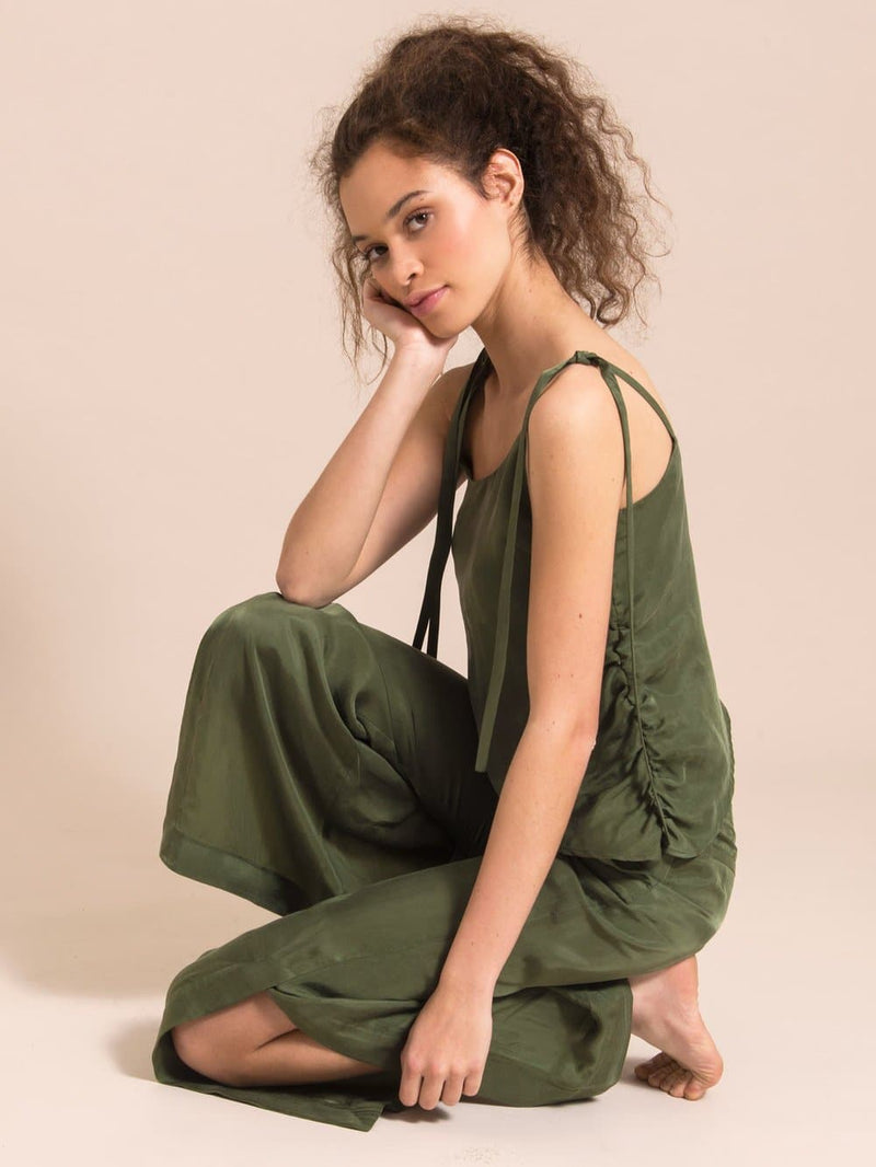 Sideshot of a model sitting on the floor in a military green set - sleeveless top with thin shoulder straps and loose, flared trousers with a slit up to the knee